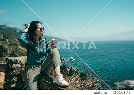 woman sitting on bench with one leg bending 43916375