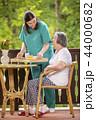 Nurse serving healthy breakfast to senior woman 44000682