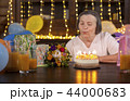 Elderly woman blowing candles at her birthday  44000683
