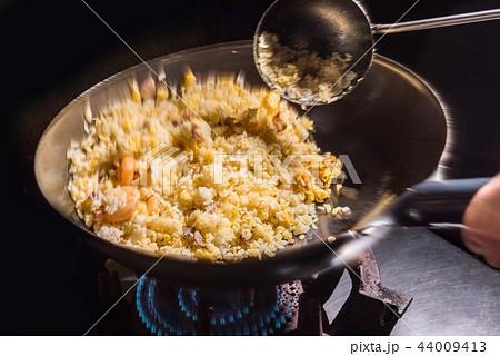 チャーハンを調理 中華鍋で炒める 44009413