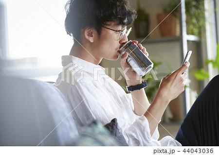 部屋でお酒を飲む男性 44043036
