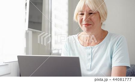 Elderly senior blond woman working on laptop computer at home. Remote freelance work on retirement 44081777