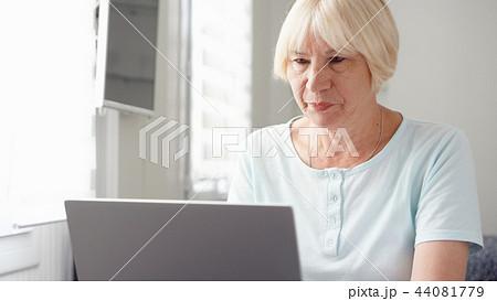 Elderly senior blond woman working on laptop computer at home. Remote freelance work on retirement 44081779