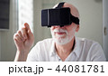 Handsome senior man in white using VR 360 glasses at home. Making browse and tap gestures 44081781
