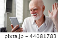 Senior man sitting at home with smartphone. Using mobile talking via messenger app. Smiling waving 44081783