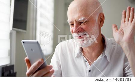 Senior man sitting at home with smartphone. Using mobile talking via messenger app. Smiling waving 44081783