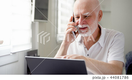 Senior man sitting at home with laptop and smartphone. Using cellphone discussing project on screen 44081786