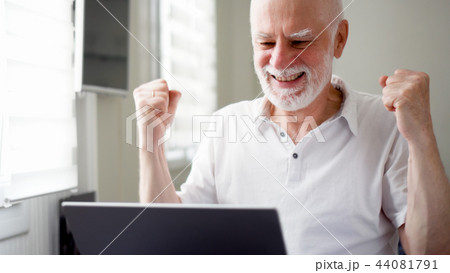 Handsome elderly senior man working on laptop computer at home. Received good news excited and happy 44081791