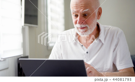 Handsome elderly senior man working on laptop computer at home. Remote freelance work on retirement 44081793