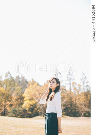 秋の草原と女性  44102094