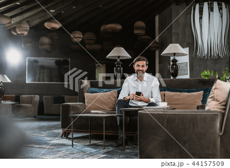 Smiling man is using smartphone in lobby 44157509