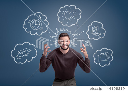 An aggressive and overwhelmed man surrounded by chalk pictures of money, car, suitcase and heart. 44196819