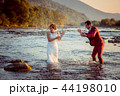 Happy newlywed couple is playing with water in the river during the sunset. Groom is splashing water 44198010