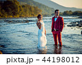 Stylish wedding couple in the river at the background of the forests and mountains during the sunset 44198012
