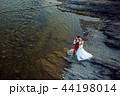 Romantic above portrait of the smiling newlyweds tenderly hugging at the river bank during the sunny 44198014