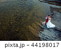 Cheerful stylish newlywed couple is hugging on the river bank during the sunny day. Above view. 44198017