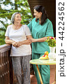 Female nurse consoling elderly woman at home 44224562