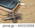 Christian cross on lavanda flowers next to Holy Bible 44224568