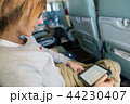 Woman reading ebook sitting inside airplane 44230407