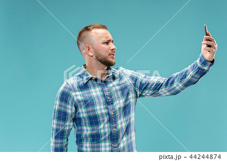 Portrait of attractive young man taking a selfie with his smartphone. Isolated on blue background. 44244874