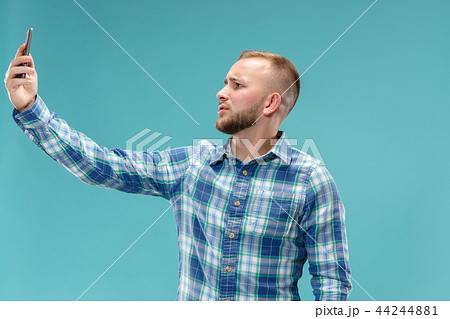 Portrait of attractive young man taking a selfie with his smartphone. Isolated on blue background. 44244881