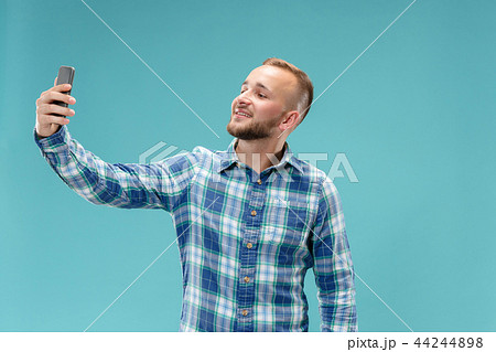 Portrait of attractive young man taking a selfie with his smartphone. Isolated on blue background. 44244898