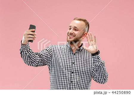 Portrait of attractive young man taking a selfie with his smartphone. Isolated on pink background. 44250890