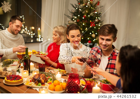 happy friends drinking red wine at christmas party 44261532