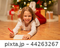 smiling girl writing christmas wish list at home 44263267