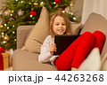 smiling girl with tablet pc at christmas home 44263268