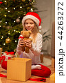 smiling girl in santa hat with christmas gift 44263272