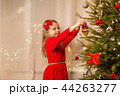 happy girl in red dress decorating christmas tree 44263277