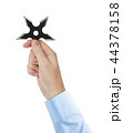 Hand is throwing ninja shuriken 44378158