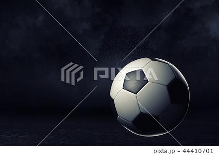 3d rendering of a single football ball on a dark background under bright spotlight. 44410701