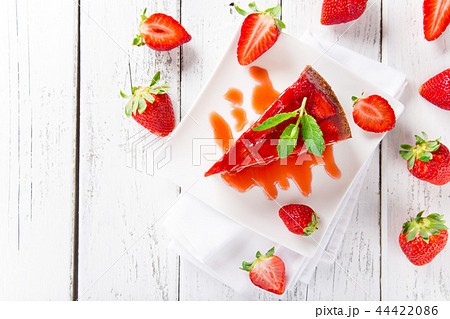 Delicious cheesecake with strawberries on wooden table. 44422086