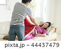 ソファで寝る妊婦にブランケットをかける夫 44437479