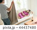 ソファで寝る妊婦にタオルケットをかける夫 44437480