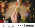 Hand Holding Bitcoin Above Christmas Decoration 44439900