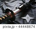黒い布の上の抜きかけた日本刀と手裏剣 44448674