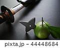 黒い板の上の抜きかけた日本刀と手裏剣が刺さったミカン 44448684