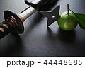黒い板の上の抜きかけた日本刀と手裏剣が刺さったミカン 44448685