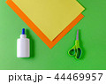color paper yellow, orange and glue with scissors for diy on green 44469957