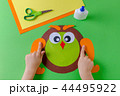 kid is making a owl with color paper, glue and scissors 44495922