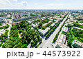 Aerial city view with crossroads and roads, houses, buildings, parks and parking lots. Sunny summer 44573922