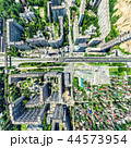 Aerial city view with crossroads and roads, houses, buildings, parks and parking lots. Sunny summer 44573954