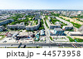 Aerial city view with crossroads and roads, houses, buildings, parks and parking lots. Sunny summer 44573958