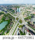 Aerial city view with crossroads and roads, houses, buildings, parks and parking lots. Sunny summer 44573961