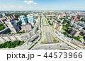 Aerial city view with crossroads and roads, houses, buildings, parks and parking lots. Sunny summer 44573966