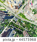 Aerial city view with crossroads and roads, houses, buildings, parks and parking lots. Sunny summer 44573968