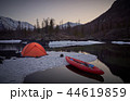 Campsite with orange tent and canoe on a lake 44619859